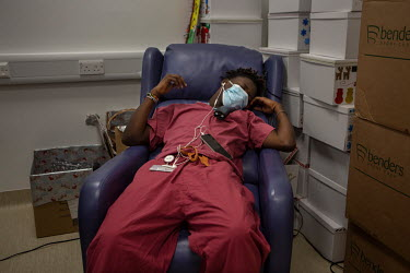 Rui Monteiro Djassi, an exhausted domestic cleaner working on the acute medicine ward at University College Hospital. He is grabbing a short nap after working for 7.5 hours without stopping. He says:...