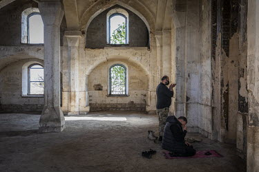 An Azerbaijani soldier and a man dressed in civilian clothing pray in a mosque in Agdam city, which had been handed back to Azerbaijan after nearly 30 years of Armenian control. The mosque was reporte...