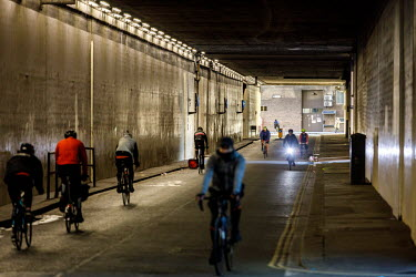 Cyclists use a road tunnel in central London.