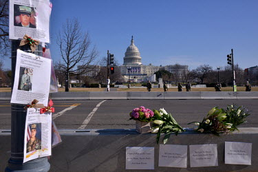 Posters outside the Capitol seeking justice for female US armed forces soldiers who died under unexplained circumstances on US army bases. To their right are flowers with peace.  Following the invasio...