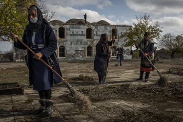Civilian workers clean up the grounds around the mosque in Agdam the day before the president of Azerbaijan was due to visit the area. Agdam and the surrounding district had been handed back to Azerba...