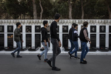 "A group of young men walk past graves in the Martyrs Alley cemetery and memorial, dedicated to those killed by the Soviet Army during 'Black January' 1990 and in the Nagorno-Karabakh War of 1988â�""19..."