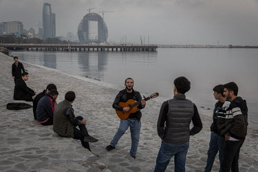 A man plays a guitar and sings while with friends on the Baku Boulevard on the banks of the Caspian Sea.