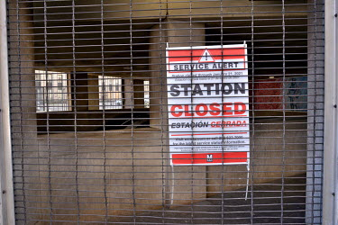 A shutter blocks the entrance to a DC metro station where a sign in English and Spanish alerts the public that the station is closed.  On the day before Joe Biden's inauguration, the city is under a l...