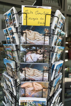 Postcards by realist painter Gustave Courbet, who was born in Ornans in 1819, for sale in a tourist shop. Postcards of his famous painting L'Origin du Monde (depicting a close-up of the genitals of a...