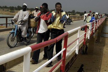 People crossing on a bridge over the Chari River, on border between Chad and Cameroon.
