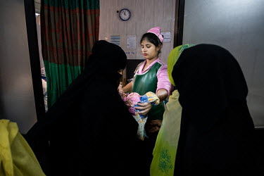 Midwife Nahida Akter hands over Rehana's newborn son to her family who have waited nervously outside during the birth at the Sadar Hospital in Cox's Bazar.