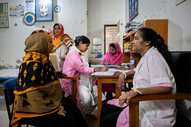 As in many workrooms, a picture of the profession's heroine Florence Nightingale adorns the wall in Moheshkhali, where Munny Akter writes notes after she has taken care of two patients.  Munny Akter i...