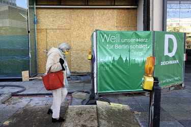 A woman wearing face mask walks past a boarded up and closed shop on the Kurfuerstendamm.