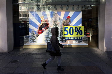 A woman walks past a sale sign in the window of a closed shop on the Kurfuerstendamm.