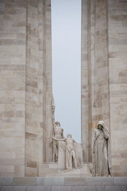 A detail of the center of the twin white pylons of the Canadian National Vimy Memorial showing the Spirit of Sacrifice and the Weeping Woman or Mother Canada mourning her dead. The monument is dedicat...