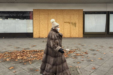 A woman wearing a fur coat and face mask walks past a boarded up and closed shop on the Kurfuerstendamm.