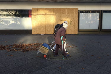 An elderly couple walks past a boarded up and closed shop on the Kurfuerstendamm.