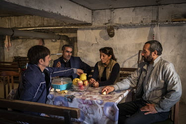 Hicran Amrahova (42) eating lunch along with her brother Mushvig and their two neighbours. The four have been living in the basement of their apartment building in the frontline city of Terter since t...
