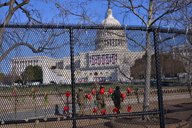 Flowers attached to fencing erected around the Capitol building to protect the 20 January 2021 inauguration of President-Elect Joe Biden, following the violent invasion by pro-Trump supporters on 6 Ja...