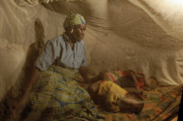 Sitting under a mosquito net, a mother watches as her three children fall asleep in the bed she shares with them, in her house in Bere.