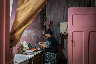 Abdullahyeva Muzaya (80) prepares a meal for her family in the kitchen of her home in an unfinished school building where several hundred families who fled previous conflicts in Nagorno-Karabakh have...