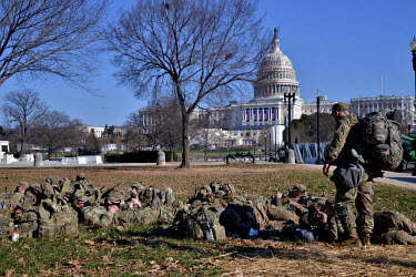 Military personnel rest near the Capitol. Following the invasion by pro-Trump supporters on 6 January 2021, and in preparation for Joe Biden's inauguration on 20 January 2021, both National Guard and...