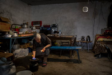 Seriyye Maharramova (73) lights a cooking gas ring in the underground bunker where she now lives along with four other people in the frontline city of Terter.