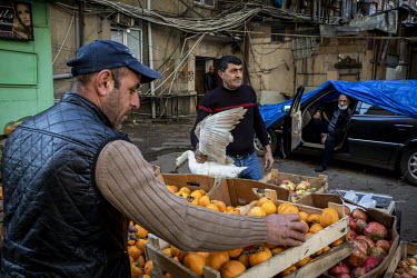 A carrying a goose and a fruit and vegetable stall in the grounds of an old dormitory building complex in the Darnagul neighbourhood of Baku, now home to thousands of refugees from Nagorno Karabakh.