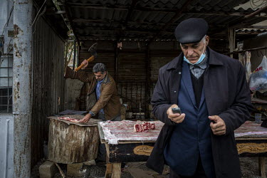 Alibala Novruzov (53) cuts meat for a customer at his butchery shop in a refugee complex in Sumgait. Novruzov fled his home in Nagorno Karabakh in the early 1990s and has lived in Sumgait with his fam...