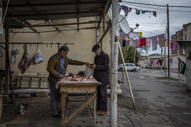 Alibala Novruzov (53) sells meat to a customer at his butchery shop in a refugee complex in Sumgait. Novruzov fled his home in Nagorno Karabakh in the early 1990s and has lived in Sumgait with his fam...