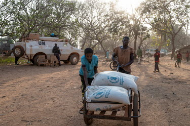 Two men return from a World Food Program partner store where they were able to exchange their food stamps for basic food. In the background is a UN peacekeeping patrol who are on guard in an area of t...