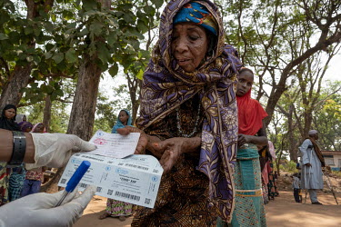 A Muslim IDP recieves stamps for food aid at a WFP distribution point.