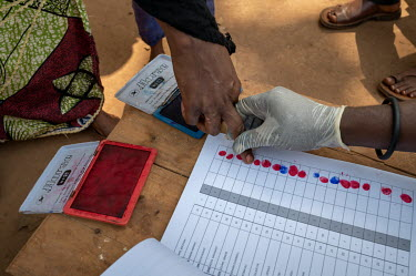 Muslim IDPs acknowlege the receipt of stamps for food aid with a finger print at a WFP distribution point.
