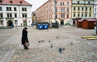 A woman watching the pigeons on the Republic Square (Namesti republiky).