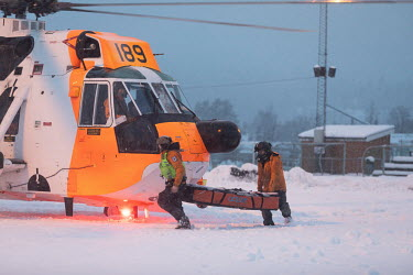 Rescue workers carry stretchers to a Sea King helicopter. A large landslide swept away a number of buildings in the town of Ask, small town about 50 km North of Oslo, and tens of people are unaccounte...