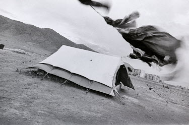 Laundry flies in the wind next to a tent owned by a Kuchi family. The Kuchi are pastoral Afghan nomads but during the last few decades wars and droughts have largely destroyed their traditional lifest...