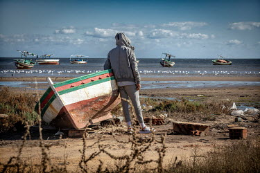 Omar, looks out to sea in a small fishing village near Sfax. He says he has already tried three times to travel illegally to Italy by boat, only 12 hours from this beach. However, each time his boat h...