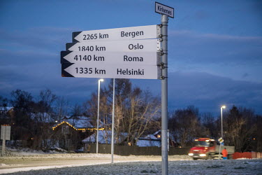 A roadside sign on the outskirts of Kirkenes indicates the distances to various European cities.