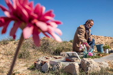 Shamseddine Marzouk stands beside the grave of Rose Marie, a young African woman, who drowned when a migrant boat sank off the north African coast. While many migrants are buried anonymously, after DN...