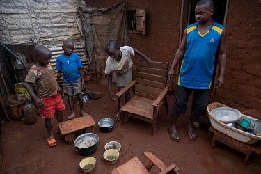 Gerry and his children about to eat a meal of cassava with sauce at their home in District 7. Gerry lost his job as a site guard and since has been struggling to feed his family. He has rented a canoe...