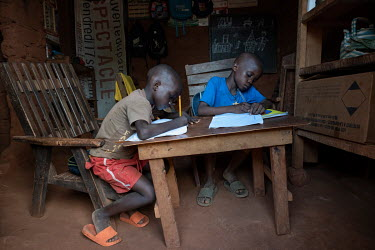 Gerry's (not pictured) children, Johnson and Miguel, doing their school work at their home in District 7. Gerry lost his job as a site guard and since has been struggling to feed his family. He has re...