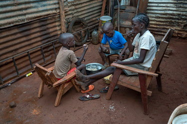 Gerry (not pictured) and his children about to eat a meal of cassava with sauce at their home in District 7. Gerry lost his job as a site guard and since has been struggling to feed his family. He has...