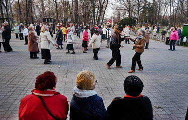 Women watch pensioners and WWII veterans take part in a large outdoor dance in Hydropark.