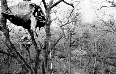 A protester sits in a camp in the trees during an attempt by activists to stop the extension of the M65 motorway being built through the Stanworth Valley.