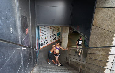 Two young people embrace in a pedestrian subway near Wenceslas Square.