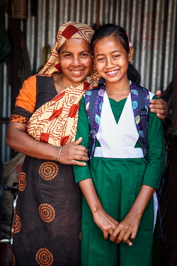 A girl, wearing her new school uniform, standing with her mother. The child has been able to stop labouring and start to attend school.
