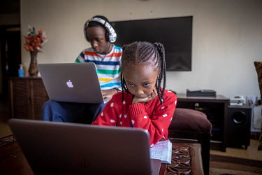 Lisa (6) and Jesse (14) Muchiri follow school lessons via Zoom on their laptops at home while the schools are closed due to the coronavirus pandemic.