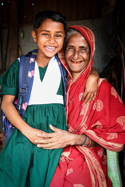 A girl, wearing her new school uniform, with her mother. The child has been able to stop labouring and start to attend school.