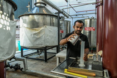 A distiller checks a batch of spirits made from agave plants at the Agave India factory, a craft distillery.