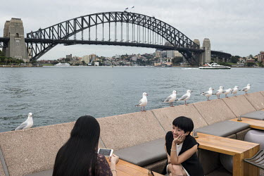 A couple sit at an outdoor cafe table overlooking the Sydney Harbour Bridge.
