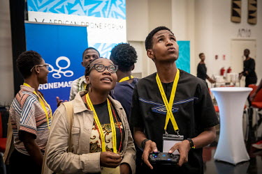 Student visitors fly a mini drone at the African Drone Forum at the Kigali Convention Centre.