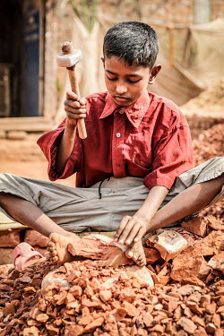 A child uses a heavy hammer to break old bricks at a crushing site (left) before he was able to stop labouring in the factory and start to attend school.