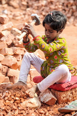 A child uses a heavy hammer to break old bricks at a crushing site (left) before she was able to stop labouring in the factory and start to attend school.