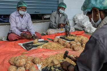 Workers crush palm sugar (jaggery) at the Agave India factory, a craft distillery.